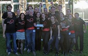 """Das Heidelberg Team mit der Trophäe des iGEM-Weltmeisters – der silberne """"Biobrick"""". Betreut wurde das Team von Prof. Roland Eils und Dr. Barbara Di Ventura (vorne links). © dkfz.de"""