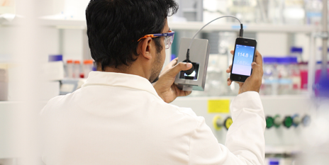 Der Forscher Jijo Vallooran misst mit einem einfachen Belichtungsmesser und einem App auf seinem Smartphone die Lichtintensität einer Probe. (Bild: Labor Prof. R. Mezzenga / ETH Zürich)