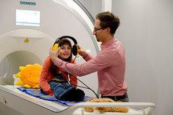 Mithilfe der Attrappe eines Hirnscanners bereitet sich eine junge Probandin auf ein Experiment vor. Michael Skeide trainiert vorab mit dem Mädchen im Kindersprachlabor, damit bei der echten Messung alles glatt geht. © MPI f. Kognitions- und Neuroswissenschaften